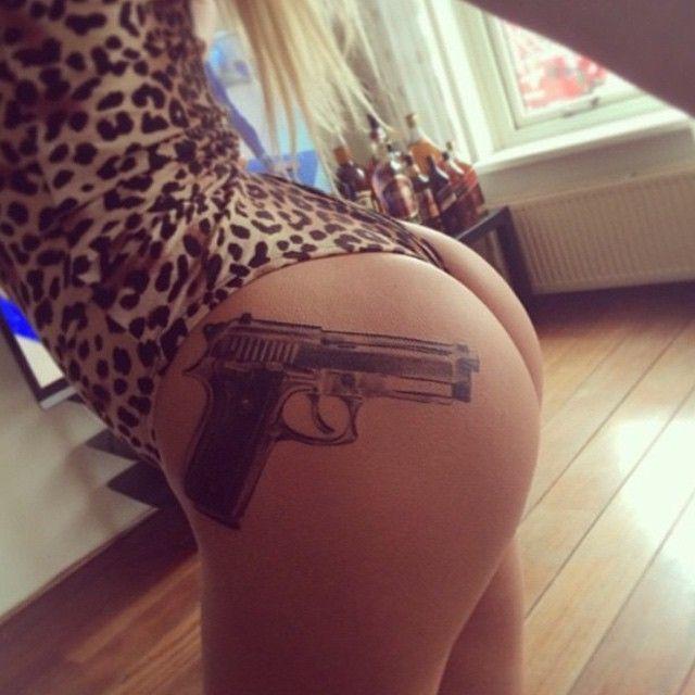Gun tattoo on boobs